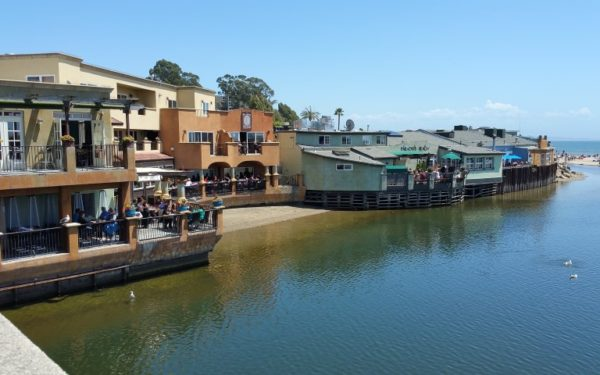 Image of Capitola from the bridge, showing the Capitola River and shops & restaurants alongside of it.